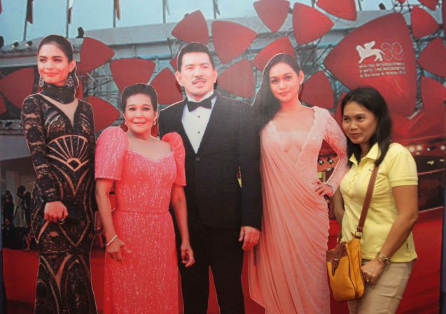 A fan takes a picture with the display of her favorite stars in Venice film fest: from left Lovi Poe, Nora Aunor, Brillante Mendoza and Mercedes Cabral. There was an exhibit of photos from THY WOMB at SM North Edsa.