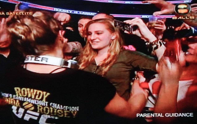 Ronda is hugged by a female fan and gets a pic taken by her iphone.