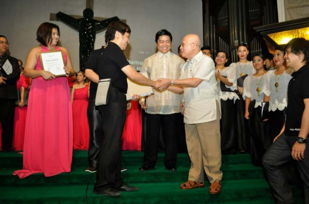 "from left: Kompositor Finance Director JED BALSAMO presents a certificate and copies of the Paggunita book to National Artist for Literature, Dr. Bienvenido Lumbera. His text ""Lumen Christi"" was set to music by Balsamo while Philippine Madrigal Singers Choirmaster Mark Anthony Carpio looks.  Contributed Photo."