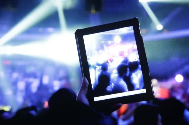 A fan uses an i-Pad to capture the action.