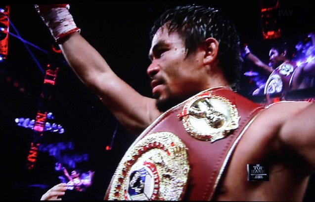 Pacquiao raises his arm in victory against Rios by unanimous decision.