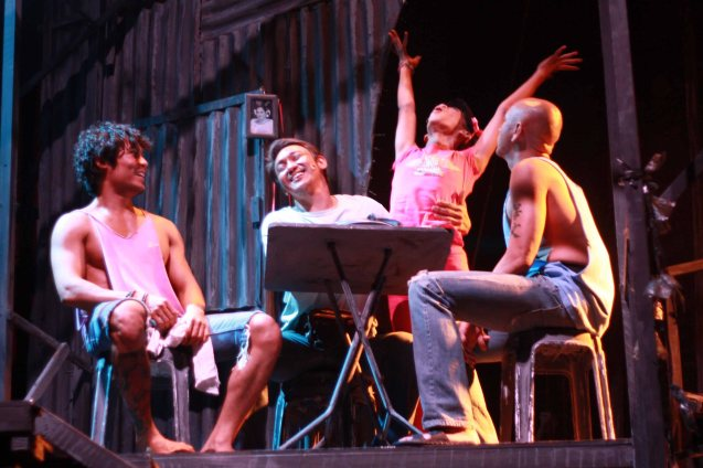 Maxie (Jayvhot Galang) standing cooks and cleans for his family seated from left: Bogs (Jay Gonzaga) , dad Paco (Roeder Camañag) and bro Boy (OJ Mariano). Catch MAXIE THE MUSICAL from Nov 9-Dec 8, 2013 at the PETA Theater Center. Photo By Jude Bautista