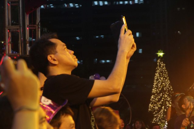 PDI Editor Poch Concepcion shoots the concert with his cell phone. Photo taken at the Eastwood City New Year Countdown to 2014, December 31 at the Eastwood Mall Open Park. Photo by Jude Bautista