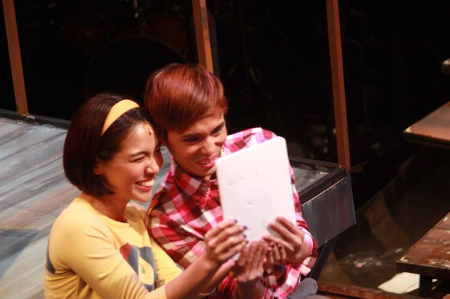 Aicelle Santos (Aileen) and Phi Palmos (Jewel) check out her vid on YouTube via a tablet. RAK OF AEGIS is a musical based on the hits of 90's band AEGIS. It will run from January 31 to March 9, 2014 at the PETA Theater Center. Photo by Jude Bautista