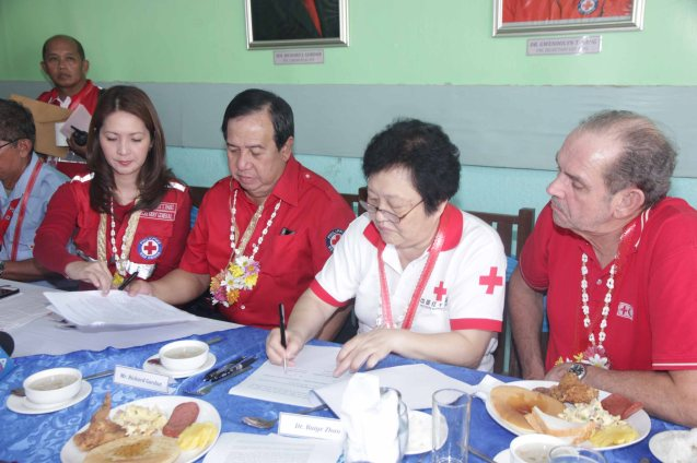 from left: Red Cross (Phil) Sec Gen. Gwendolyn Pang assists Red Cross (Phil) Chairman and CEO Richard Gordon and Red Cross (China) EVP & Intl Red Cross VP Dr. Baige Zhao sign agreement as IFRC Rep Marcel Fortier looks on. Photo taken last February 10, 2014 in Tacloban, Leyte by Jude Bautista.