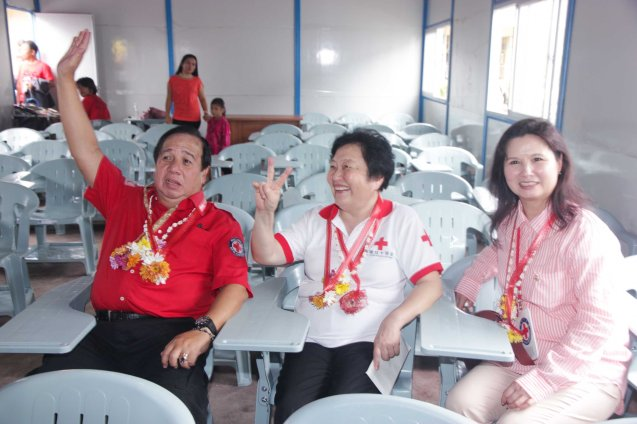 from left: Red Cross (Phil) Chairman and CEO Richard Gordon, Red Cross (China) EVP & Intl Red Cross VP Dr. Baige Zhao and Red Cross (HK) Deputy Chair Madame Ivy Wu Kwok Sau-ping test out the brand new desk and chairs donated by HK Red Cross at San Jose Central School in Tacloban. Photo taken last February 10, 2014 by Jude Bautista.