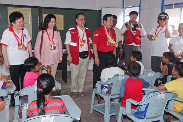 from left: Red Cross (China) EVP & Intl Red Cross VP Dr. Baige Zhao, Red Cross (HK) Deputy Chair Mdme Ivy Wu Kwok Sau-ping, Red Cross (Phil) Sec. Asst. /Board of Dir. Atty Inky Reyes, Red Cross (Phil) Chairman and CEO Richard Gordon, Red Cross (China) Head of Gen Administration Yi Song and Red Cross (China) Head of Operations Zhang Ming spends time with kids of San Jose Central School in Tacloban. Photo taken last February 10, 2014 by Jude Bautista.