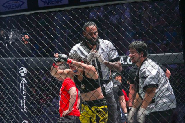 Julaton bows to the crowd after getting the TKO win against Saber. Behind her is trainer Angelo Reyes and for Miami Heat Ronnie Turiaf. The historic fight was during ONE FC: Rise of Heroes at the Mall of Asia Arena last May 2, 2014. Photo by Jude Bautista