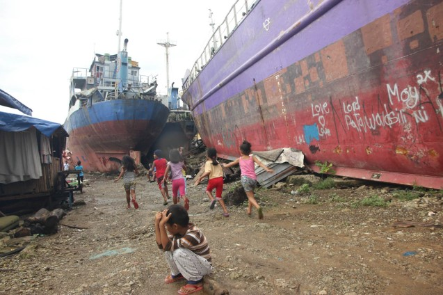 Kids play between ships that were tossed on shore during storm surge nearly a year ago. Photo by Jude Bautista