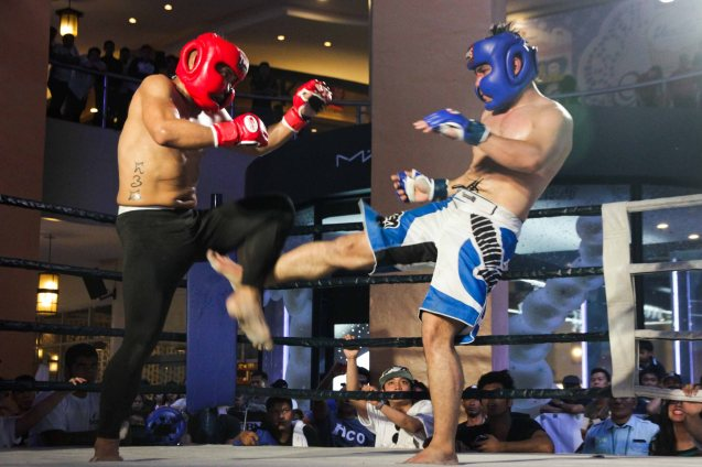 Ken Menia of Espinosa MMA (blue) lands a leg kick on Carl Jose Lalu of Tiger MMA (red) The first ever ABS CBN Sports & Action- Rexona Fight Expo was held last November 8, 2014 at the Eastwood City Open Area. Photo by Jude Bautista