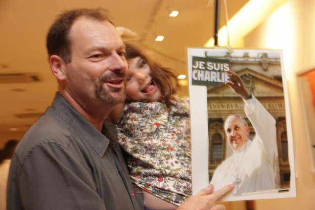 French father and daughter show their solidarity during the candle lighting ceremony for the victims of the Charlie Hebdo attack held at Alliance Francaise de Manille last Januarry 14, 2015. Photo by Jude Bautista