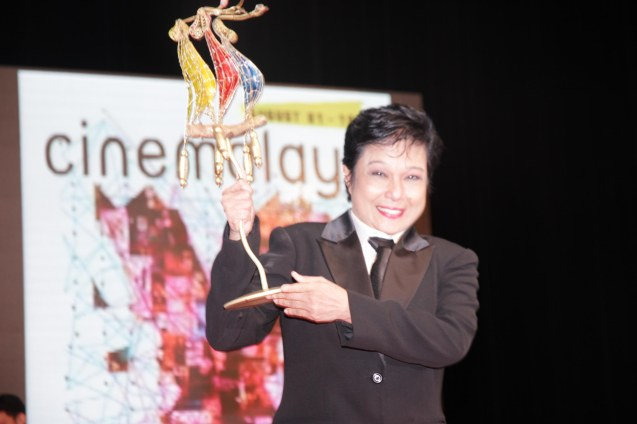 Nora Aunor raises her Cinemalaya Best Actress Award for HUSTISYA (Director's Showcase Category) at the CCP last August 2014. Photo by Jude Bautista