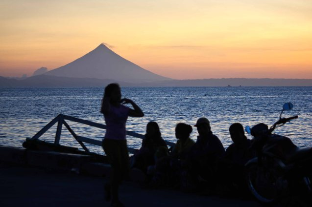 Mayon Volcano can be seen from the port of Claveria Burias, foreground: Passengers wait to board lantsa-May 18, 2015. Photo by Jude Bautista