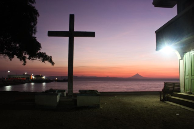 Mayon Volcano can be seen from the port of Claveria, Burias, in the foreground is a concrete cross-May 19, 2015. Photo by Jude Bautista