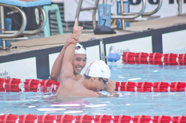 Jessie manages to raise his brother Dexter's hand but results favored the Atenean at the 200m Freestyle. Photo was taken October 24, 2015 during 78th UAAP Swimming competitions at the Rizal Memorial Swimming Complex. Photo by Jude Bautista