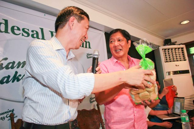 Wilson Lee Flores gives a pack of fresh pugon-baked pandesal as a goodluck token to Sen. Bong bong Marcos. Photo by Chris Lucas
